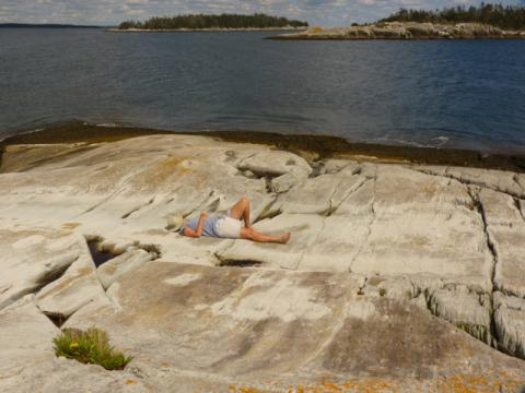 Woman sleeps on a rocky island